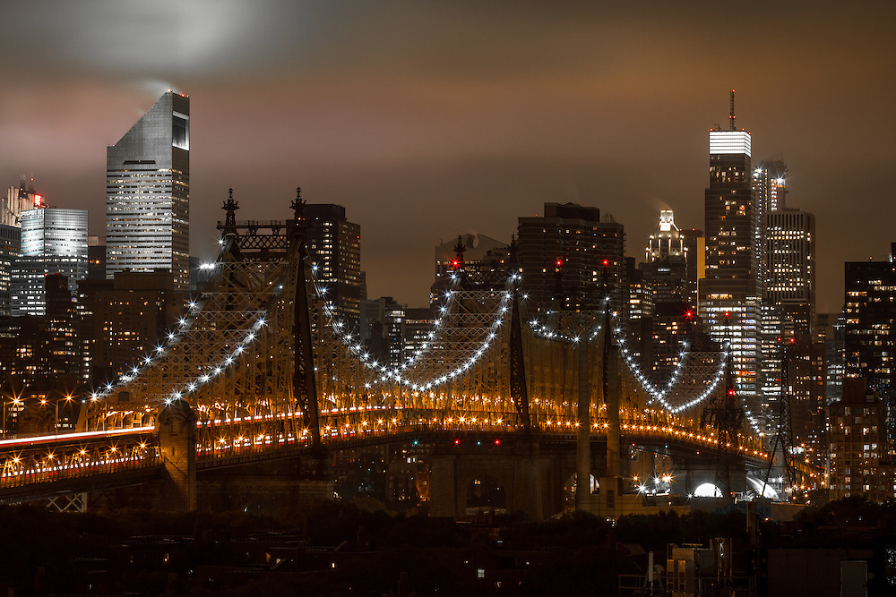 The New York City skyline and the Queensboro bridge at night on a Fall evening as the city lights light up the stormy clouds overhead.