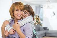 Loving daughter embracing mother at home