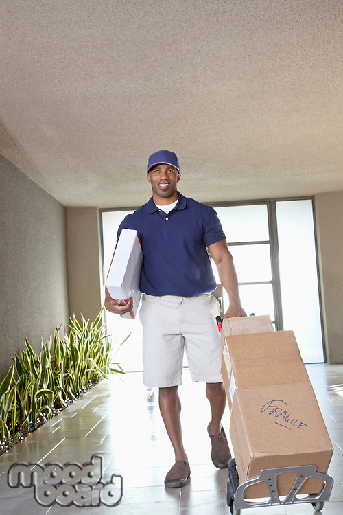 Happy African American delivery man with packages