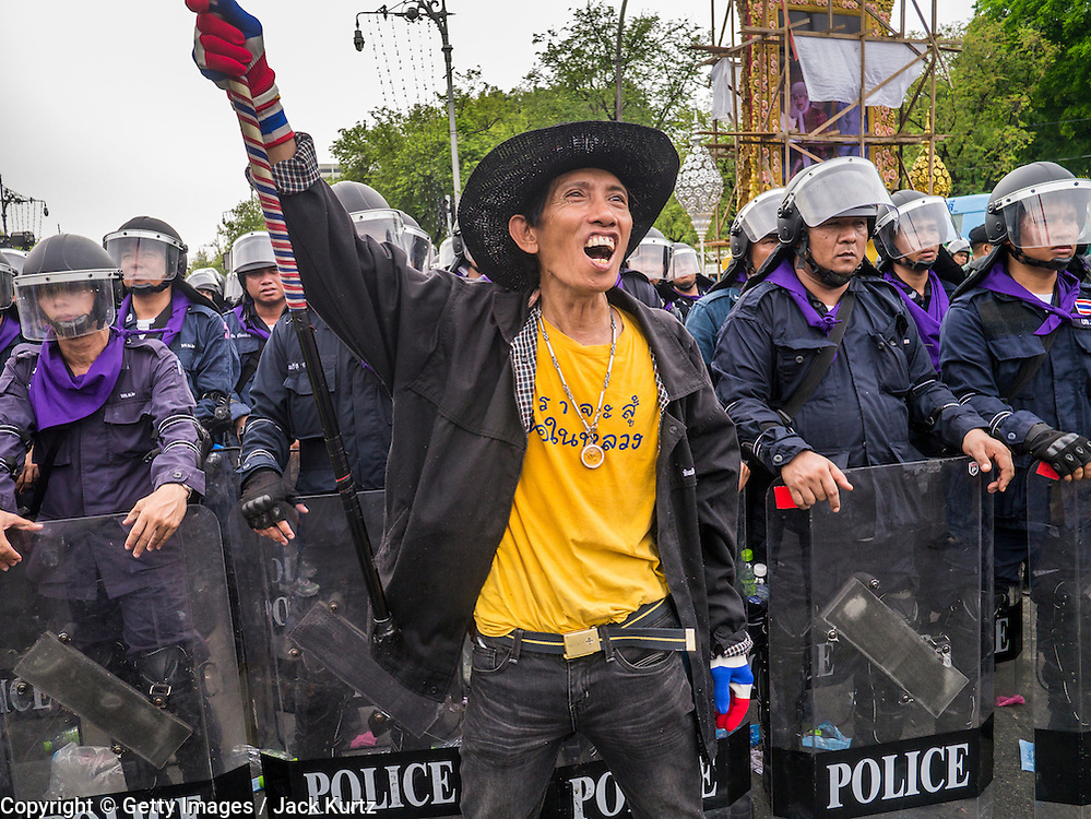 24 NOVEMBER 2012 - BANGKOK, THAILAND: An anti-government protester in front of a phalanx of riot police during a large anti government, pro-monarchy, protest  on November 24, 2012 in Bangkok, Thailand. The Siam Pitak group, which sponsored the protest, cited alleged government corruption and anti-monarchist elements within the ruling party as grounds for the protest. Police used tear gas and baton charges againt protesters.       PHOTO BY JACK KURTZ