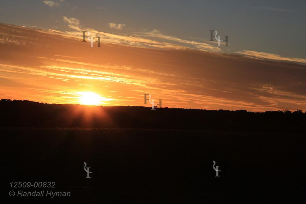Sun sets behind ridge like a golden flare on an Ozark farm near Belgrade, Missouri.