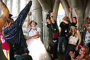 A crowd of people cheer inside an inflatable church,Boomtown, Matterley Estate, Alresford Road,Winchester, Hampshire, UK, August, 2010