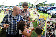 From left, Greg Bell, 30 and his brother Leighton Bell, 25 of Bristol, Pennsylvania show their nice Sabrina Bell, 9 pictures of themselves as boy scouts during the Boy Scout Troop 180's 50th Anniversary celebration at the VFW Saturday August 22, 2015 in Croydon, Pennsylvania. (Photo by William Thomas Cain)