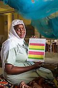 Medical attendant Sophia showing one of the new born checklists. NICU (Neonatal Intensive Care Unit) ward. St Walburg's Hospital, Nyangao. Lindi Region, Tanzania.