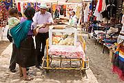 24 APRIL 2005 - SAN CRISTOBAL DE LAS CASAS, CHIAPAS, MEXICO: A snack vendor sells orange slices to a Mayan Indian family in front of Templo Santo Domingo in San Cristobal de las Casas, Chiapas, Mexico. San Cristobal is the center of the Chiapas highlands and an important indigenous community. PHOTO BY JACK KURTZ