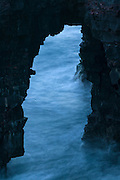 A long exposure captures the motion of Pacific Ocean waves crashing through the Hōlei Sea Arch in Volcanoes National Park, Hawai`i. The Hōlei Sea Arch is about 90 feet (27 meters) tall and quite young. The erosive force of the waves created the arch within the past 100 years. The lava cliff itself is only about 550 years old. Hōlei is the name for a small plant in the milkweed family.