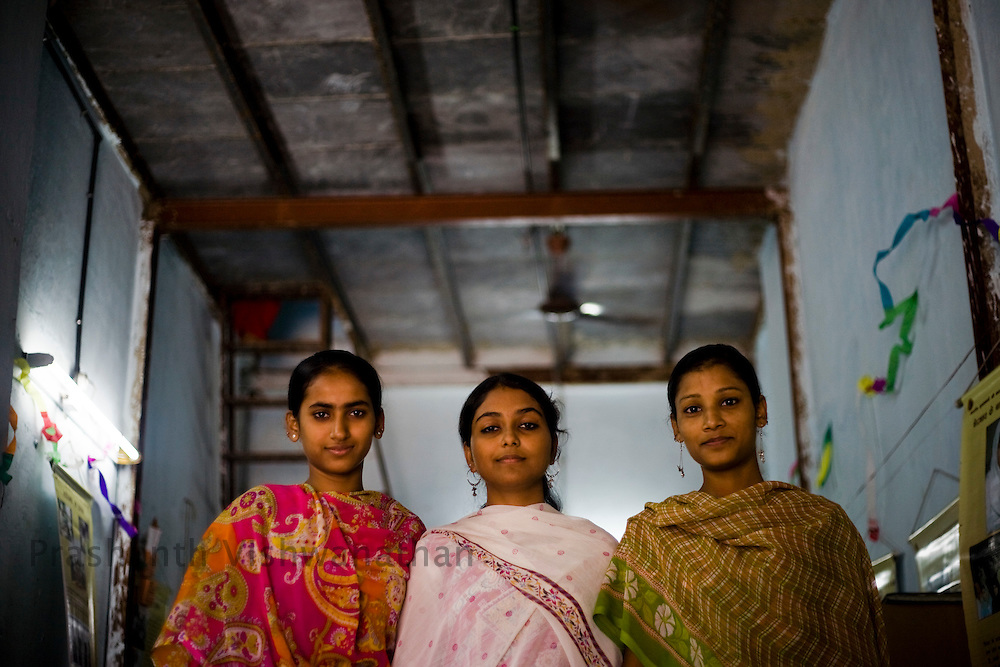 """Aisha Khan 18 (R), Shabnam Sayyed 19 (L) and Firoz Sheik 22 (C) in the community center, in Mumbai, India, on Tuesday February 11, 2009. A new group of girls who have been benifitted out of the scolarship programmes for education from the mandal. These girls inspire and pool in other girls who have quit studies and have not been able to pursue higher education. They then guide them into programmes of the mandals like learning the Muslim Domestic Law, Indian Divorce Law, Career Guidance, Sexuality, Self Defense and many such training programmes. Their group consists of 5 girls till now..Aisha khan 18 says, she was very shy before the exposure but now she can travel anywhere for meeting. Convince parent, make her own decisions and be confident. She adds shyly """"my parents dont mind now even if I talk to boys."""". Photographer: Prashanth Vishwanathan"""