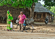 In rural Tanzania, a man and a woman converse at a roadside.  The man holds his bicycle.