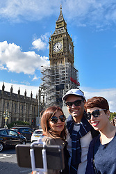 © Licensed to London News Pictures. 30/09/2017. London, UK. Tourists take a selfie by the Elizabeth Tower, covered in scaffolding and home of Big Ben, as remedial work continues.  A new statement released by Parliament states that the cost of renovations has more than doubled to £61m as contractors have found the work to be more complex and extensive compared to the 2016 estimate of £29m.  Photo credit : Stephen Chung/LNP