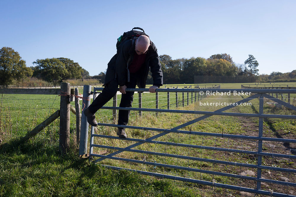 A country walker scales a farm gate from one field to another, on 21st October 2018, near Hollingbourne, Kent, England.