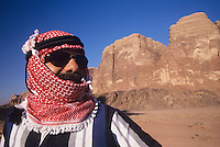 Arab Man in turban Wearing Sunglasses standing in desert landscape