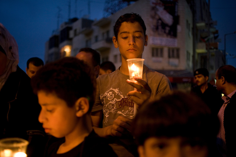 A Young Palestinian boy takes part in a candle lit vigil that marks the Al-Nakba in the West Bank city of Ramallah on 16th May 2008