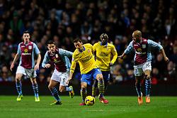 *CAPTION CORRECTION* Arsenal Midfielder Mesut Ozil (GER) is challenged by Aston Villa Midfielder Ashley Westwood (ENG) during the first half of the match - Photo mandatory by-line: Rogan Thomson/JMP - Tel: Mobile: 07966 386802 - 13/01/2014 - SPORT - FOOTBALL - Villa Park, Birmingham - Aston Villa v Arsenal  - Barclays Premier League.