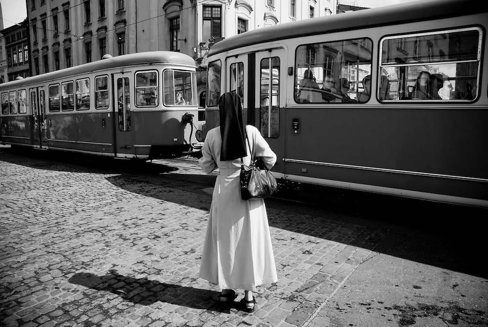 A nun waits for trams to pass in Krakow, Poland. July 2009.