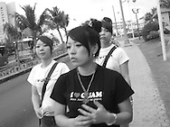 """Japanese tourists wearing """"I love Guam"""" t-shirts walking in Tumon, Guam, on Saturday, Mar. 10, 2007.  Sometimes known as 'America in Asia', Guam is a popular destination for Japanese tourists ( accounting for approx 90% of the island's visitors) with average visitor numbers from Japan approaching 1million.  The island, a 3.5 hour flight from Japan, has more than 20 large hotels and numerous duty-free shopping malls catering to the Japanese tourists predilection for designer brand name goods, as well as golfing and other water based entertainment features. In 2007-2008 US military personal currently stationed in the Japanese Okinawan Islands will relocate their bases and operations  to Guam, helping to stabilise the island's economy which suffered after tourism decreased in recent years due to a  fear of flying by Japanese post 9-11 World Trade Centre disaster, a 2003 typhoon and the SARS disease outbreak in Asia."""