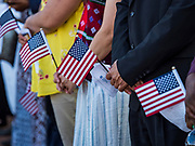 04 JULY 2019  - DES MOINES, IOWA: People about to be naturalized as American citizens hold their flags before the ceremony. Thirty people became US citizens during a naturalization ceremony at the Iowa Cubs game in Des Moines. The naturalization ceremony is an Iowa Cubs 4th of July tradition. This is the 11th year they've held the ceremony.         PHOTO BY JACK KURTZ
