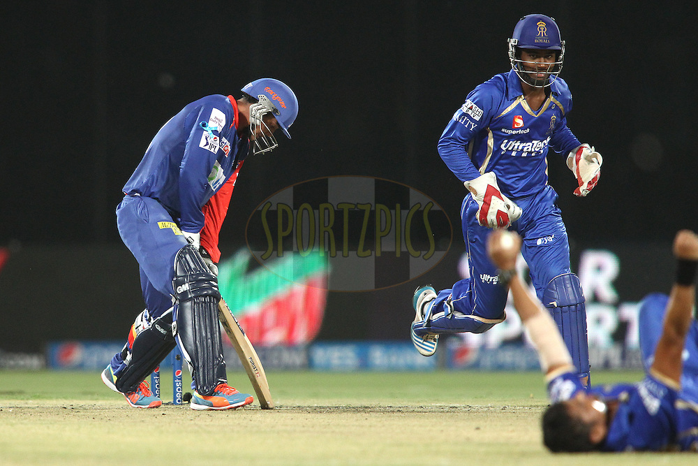 A dejected Quinton de Kock of the Delhi Daredevils after losing his wicket as Pravin Tambe of the Rajasthan Royals celebrates during match 23 of the Pepsi Indian Premier League Season 2014 between the Delhi Daredevils and the Rajasthan Royals held at the Feroze Shah Kotla cricket stadium, Delhi, India on the 3rd May  2014<br /> <br /> Photo by Shaun Roy / IPL / SPORTZPICS<br /> <br /> <br /> <br /> Image use subject to terms and conditions which can be found here:  http://sportzpics.photoshelter.com/gallery/Pepsi-IPL-Image-terms-and-conditions/G00004VW1IVJ.gB0/C0000TScjhBM6ikg