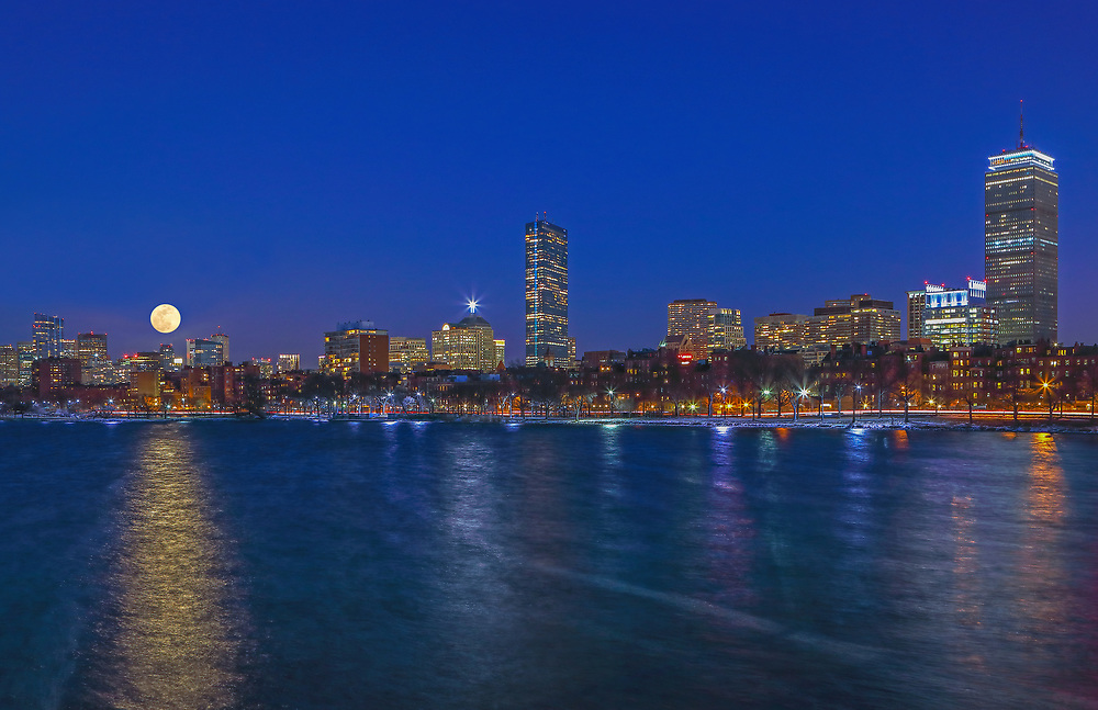 Sunday, 12 March 2017, I was on a mission to capture the moon rising across the Boston skyline. It was a frigid cold night and in the single digits. This was probably the main reason that there were not many people on the street, no bikers, walkers and runners and yes, I did not spot any other photographer that night. In this moon and skyline photography image, I selected a wide view of the Hub that includes the familiar Charles River skyline landmarks such as the John Hancock tower and Prudential Center in the Back Bay and the newly constructed Millennium Tower, one of Boston&rsquo;s latest landmarks and building architecture. <br />