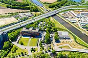 Nederland, Noord-Brabant, Den Bosch, 13-05-2019; Knooppunt Hintham, half-sterknooppunt. Het knooppunt is onderdeel van de Ring 's-Hertogenbosch en verbindt rijksweg A59 (in oostelijke richting) met rijksweg A2 (buiten beeld). Maximakanaal, in het hart van het knooppunt Heijmans Materieel Beheer, links hoofdkantoot van Heijmans.<br /> Hintham junction, near Den Bosch.<br /> <br /> aerial photo (additional fee required); luchtfoto (toeslag op standard tarieven); copyright foto/photo Siebe Swart