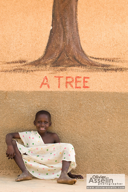 A girl sits against a wall painting of a tree.