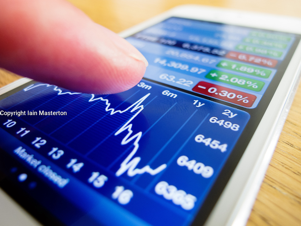Detail of iPhone 5 smart phone screen showing stock market financial data on chart using finance app
