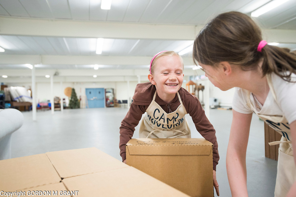 Ryder Stella, 6, left, and Cara Heneghan, 7, members of the non-profit Camp SoulGrow, help to stock food at the Montauk Food Pantry at St. Therese Church in Montauk, March 14, 2016.