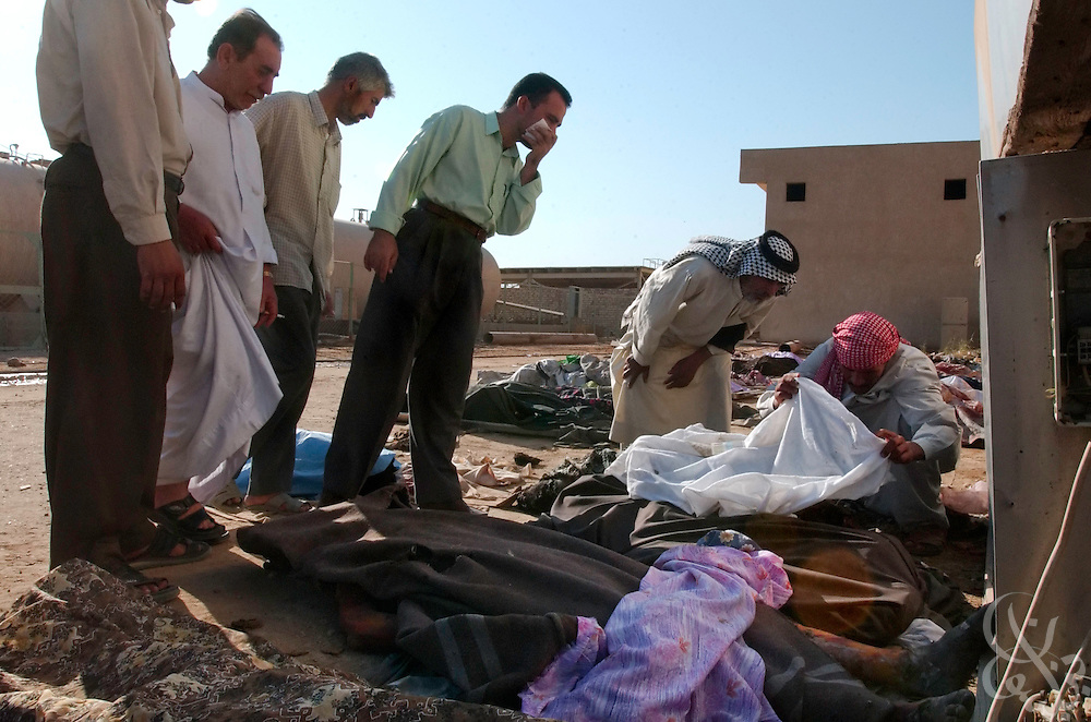 Iraqi men try to identify the bodies of their relatives in a makeshift overflow morgue at the hospital on August 30, 2003, following yesterday's massive car bombing at the nearby Imam Ali shrine that killed one of the most important Shiite clerics in Iraq, Mohammed Baqir al-Hakim and more than 100 others.