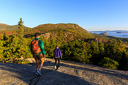"A young couple hiking on ""The Beehive"" in fall in Maine's Acadia National Park.`"