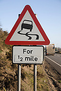 Red triangular road sign warning of slippery road surface ahead for half a mile, UK