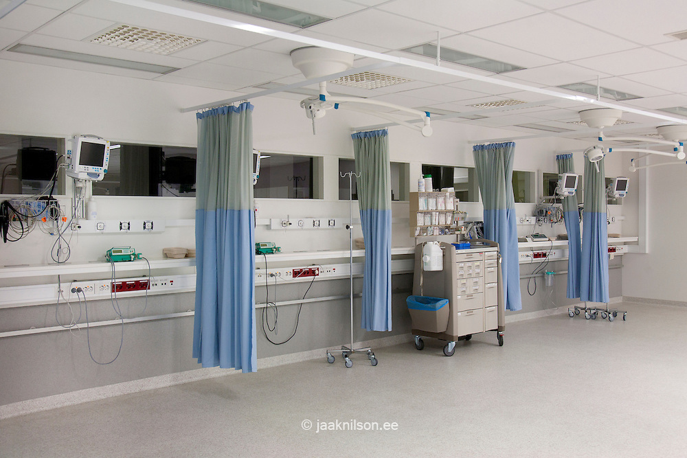 Recovery room in Tartu university hospital. Drapes, curtains around patient bays. Electronic monitoring equipment and medical supplies.