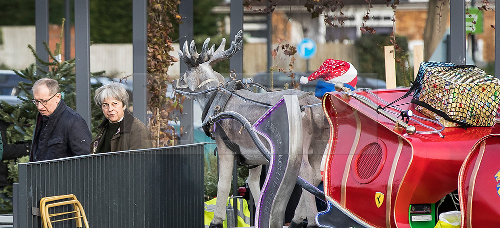 © Licensed to London News Pictures. 09/12/2017. Maidenhead, UK. Prime Minister Theresa May and her husband Philip pass a charity replica reindeer and sleigh as they shop in her constituency. Photo credit: Peter Macdiarmid/LNP