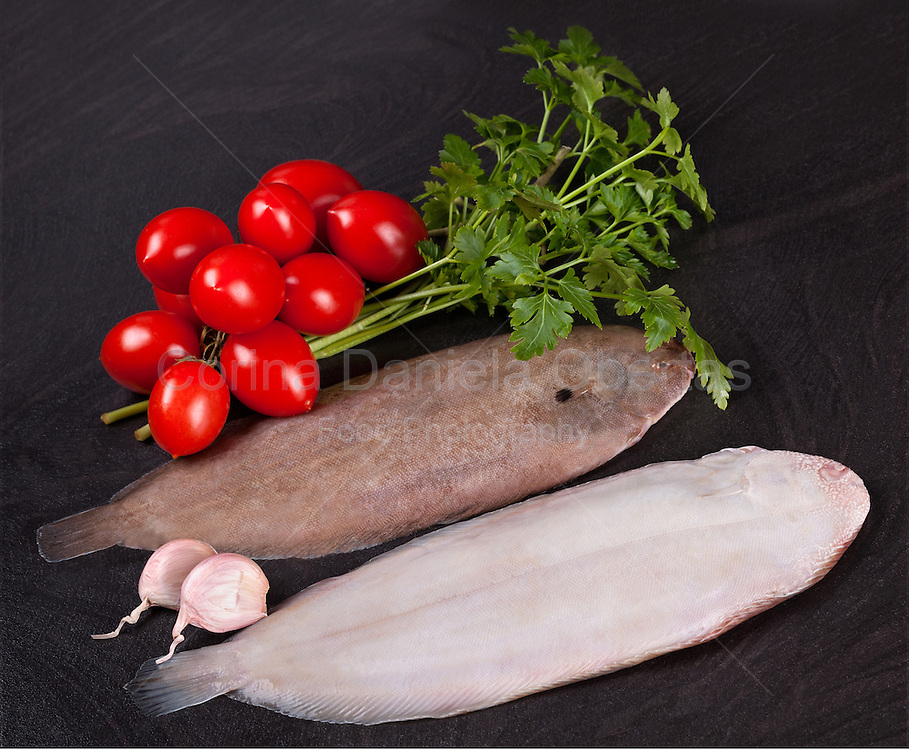 Raw common sole with fresh tomatoes, parsley and garlic, on black background.