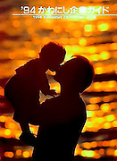 Cover photo for a Jananese publication. A father holding his infant son is silhouetted against the sparkling sunlight on the ocean.