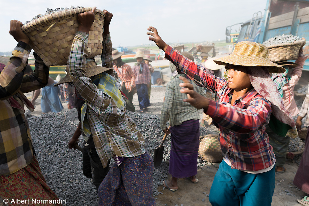 Young girls help each other loading baskets full of gravel on to each others head, Ayeyarwaddy River Jetty