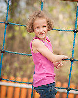 Young girl on climbing net turning to face camera
