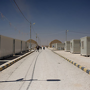 August 09, 2013 - Zarqa, Jordan: Syrian refugees pass by a row of portacabins at the Mrigb Al-Fuhud refugee camp, also known as Emirates-Jordanian camp, 20 kilometres east of the Jordanian city of Zarqa.<br /> The 10 million USD camp, which has 750 caravans, a hospital, and a school and can take up to four thousand people, first opened in April 2013 and was paid for by the United Arab Emirates. Work is underway to house a total of 20 thousand by the end of the year.<br /> In contrast with the two other camps in the area, Mrigb Al-Fuhud as been classified by many as a 'five star' camp due to impressive housing facilities provided to the refugees. (Paulo Nunes dos Santos/Al Jazeera)