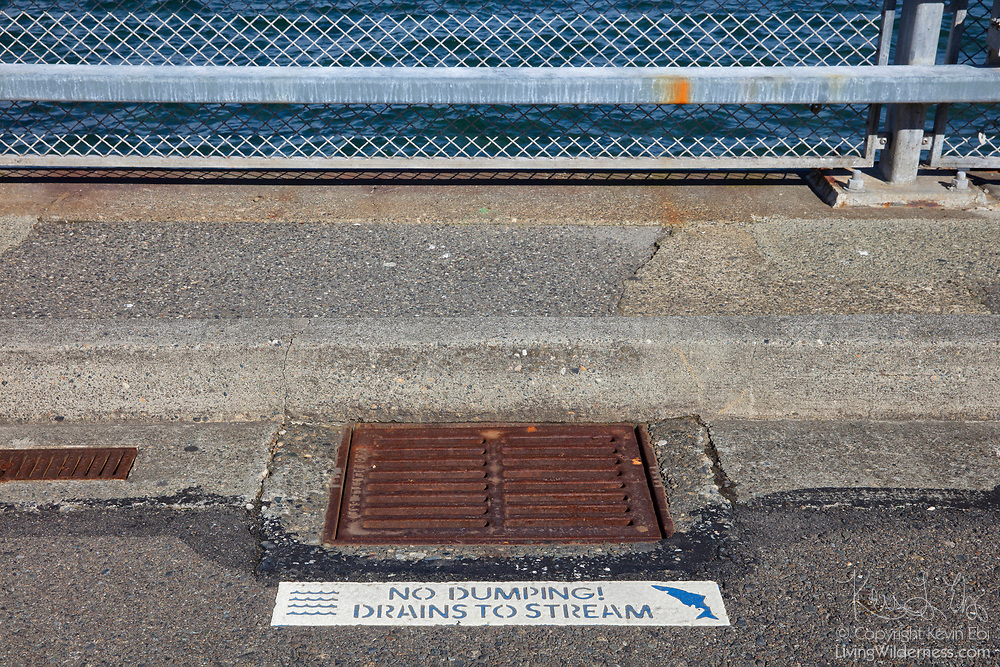 "With the water of Puget Sound in the background, a sign next to a stormwater drain warns people not to dump toxic materials. The sign reads ""No dumping! Drains to stream."""
