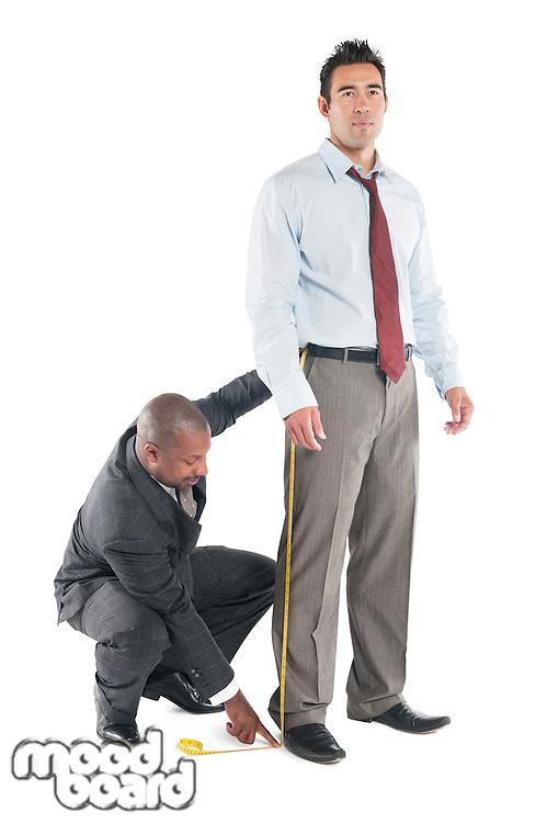 Tailor taking measure leg of customer