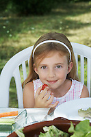 Portrait of girl (5-6) sitting at dinner table in garden