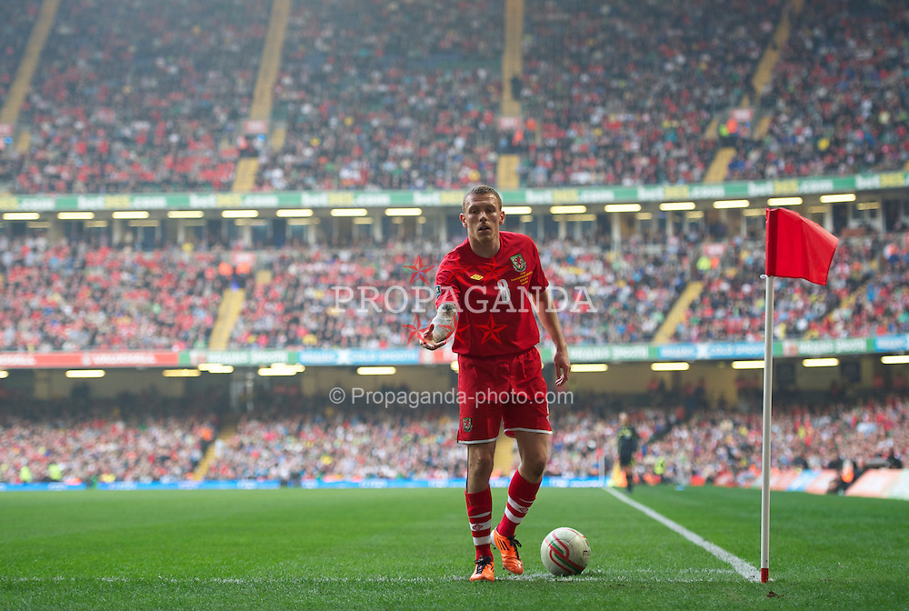 CARDIFF, WALES - Saturday, March 26, 2011: Wales' Craig Bellamy picks up a coin that was thrown at him by an England hooligan during the UEFA Euro 2012 qualifying Group G match at the Millennium Stadium. (Photo by Chris Brunskill/Propaganda)
