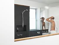 Man looking at himself in bathroom mirror half-length