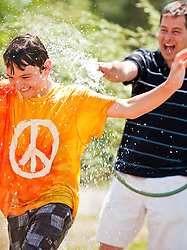 Boy in a peace tee shirt running from a man spraying water from a sprinkler hose outdoors