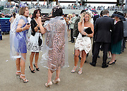 © licensed to London News Pictures. ASCOT, UK.  16/06/11. Women wrap up against the rain. Ladies Day at Royal Ascot 16 June 2011. Royal Ascot has established itself as a national institution and the centrepiece of the British social calendar as well as being a stage for the best racehorses in the world. Mandatory Credit Stephen Simpson/LNP