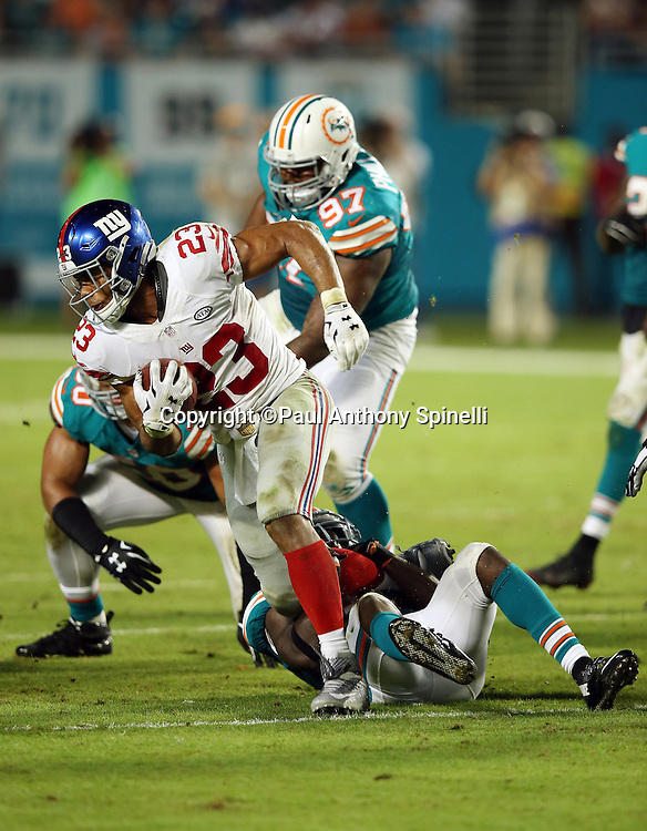 New York Giants running back Rashad Jennings (23) tries to elude a gang tackle by Miami Dolphins defensive end Olivier Vernon (50), Miami Dolphins defensive tackle Jordan Phillips (97), and Miami Dolphins free safety Michael Thomas (31) on a third quarter run during the NFL week 14 regular season football game against the Miami Dolphins on Monday, Dec. 14, 2015 in Miami Gardens, Fla. The Giants won the game 31-24. (©Paul Anthony Spinelli)