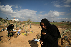 A woman is seen visiting the grave of several family members killed by Israeli artillery fire, Beit Hanoun, Gaza Strip, Palestinian Territories, Nov. 16, 2006. Israel blames the deaths on a targeting error and expresses regret. According to Human Rights Watch, since September 2005, Israel has fired about 15,000 rounds at Gaza while Palestinian militants have fired around 1,700 back.
