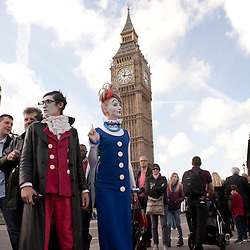 London, UK - 24 October 2013: Pavel Ivanov (L) and Ekaterina Voevodkina (R) surrounded by amused and curious tourists on Westminster Bridge.