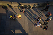 The long shadows of strangers as they walk along London's Southbank.