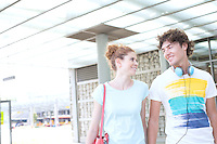 Smiling couple looking at each other while walking in city