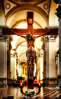 """""""Crucifix beyond the vestibule of the Abbey of Santa Giustina – Padua""""… <br /> <br /> Our Pilgrimage finally arrived in Padua and after lunch we discovered the Abbey of Santa Giustina attached to the Basilica built in the 6th century. It contains the relics of multiple saints (including those of St. Luke the Evangelist). Shaped in the form of a Latin cross, the prodigious Basilica of St. Giustina is one of the most colossal in all of Christianity. The grandeur of the building is enhanced by the Prato della Valle which it overlooks. There are 3 main chapels: the presbytery, and 2 chapels for Saints Luke and Matthew that form the transepts and each aisle has six small chapels. The Abbey and the Basilica of St. Anthony were two of my foremost surprises and a must see on a Pilgrimage to Italy. Unfortunately, pictures were allowed only in St. Giustina, but not in the latter. Initially, I was a bit overwhelmed at the imposing wide open space of the Basilica. The high altar seemed an eternity away. It is difficult to give one a perspective of just how spacious and immense many of these basilicas can be, not only in pictures, but in words. The colorful geometric marble floor leads one to the main altar, but only adds to the great depth, size, and dimension of the Basilica. A curiously placed Crucifix standing about 6' tall is located just inside the colossal nave and appears diminutive below the 26 pillars supporting the 8 cupolas. As most basilicas are traditionally dark depending on the sunlight, the Crucifix was almost a complete faint silhouette only lit by the dome windows above the altar. Standing as close as possible with a telephoto perspective, I was able to reverse the impression of size and portray the grandiosity Christ deserves, as well as the original artist. The distant window light bled over the body and illuminated the darkness. The glow of the original beauty has become radiant. Framed by the brilliant distant archways, the Crucifixion becomes transformed"""