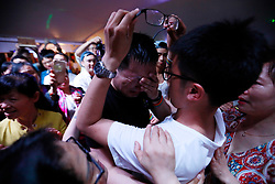 Chinese gay couple Tank (C) and Dazhe (L) become emotional after kissing each other openly during a party after a LGBT (lesbian, gay, bisexual and transgender) mass wedding organised by the Parents and Friends of Lesbians and Gays (PFLAG) China organisation on a cruise in open seas on route to Sasebo, Japan, 15 June 2017.